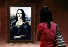 <p>Um visitante olha para uma versão em holográfico da Mona Lisa em Pequim. 21/08/2009. REUTERS/David Gray</p>