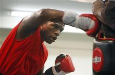 <p>Boxer Floyd Mayweather Jr. of the U.S. hits a body pad worn by assistant trainer Nate Jones during a workout in his gym in Las Vegas, Nevada, June 11, 2009. REUTERS/Las Vegas Sun/Steve Marcus</p>