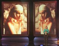 <p>A television technician stands on the stage under images of Tammy Wynette during rehearsals for the 32nd Country Music Association's awards show at the Grand Ole Opry House in 1998. REUTERS/File</p>