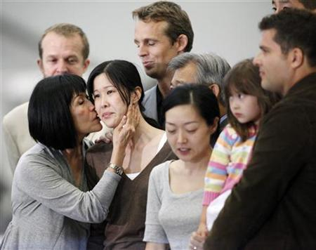Freed U.S. journalist Laura Ling (2nd L) is kissed by her mother Mary as she stands with fellow freed U.S. journalist Euna Lee (3rd R) with their family after arriving from North Korea in Burbank, California August 5, 2009. REUTERS/Danny Moloshok