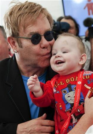 Pop singer Elton John kisses baby Lev during a news conference at a hospital for HIV-positive children in the town of Makeyevka outside Donetsk, September 12, 2009. The singer announced during the news conference that he and his partner are eager to adopt Lev though they have never thought of an idea of the adoption before. REUTERS/Handout