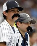 <p>Due piccoli tifosi dei Ney York Yankees con baffi finti. REUTERS/Ray Stubblebine</p>