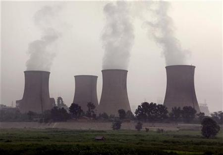A small house can be seen in front of a coal-burning power station located on the outskirts of Beijing August 17, 2009. REUTERS/David Gray