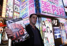 "<p>American writer Jake Adelstein poses with his book ""Tokyo Vice"" at a red-light district in Tokyo October 9, 2009. A 12-year stint covering crime for Japan's biggest daily newspaper, the Yomiuri Shimbun, brought Adelstein into contact with the seamy side of Tokyo that most Westerners never see, from loan sharking to murders to trafficking in sex workers. Picture taken October 9, 2009. REUTERS/Kim Kyung-Hoon</p>"
