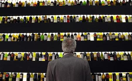 A man looks at bottles of wine on display at the Vinitaly wine expo in Verona April 3, 2009. REUTERS/Alessandro Garofalo