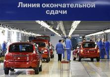 <p>Рабочие сматривают автомобили на выходе с конвейера на заводе АвтоВАЗа в Тольятти 25 сентября 2009 года. Правительство РФ, пообещавшее накануне почти $2 миллиарда на спасение АвтоВАЗа, возьмет большую часть этой суммы из бюджета, но будущее убыточного флагмана автомобилестроения связывает с продажей контроля стратегическому инвестору, скорее всего - Renault, сказал Рейтер источник в правительстве. REUTERS/Denis Sinyakov</p>