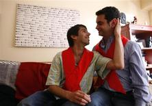 <p>Alex Freyre (L) caresses his partner Jose Maria Di Bello at their home in Buenos Aires, November 13, 2009. A REUTERS/Marcos Brindicci</p>