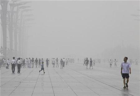 A thick haze can be seen as tourists and locals walk along the Olympic Green area in Beijing, August 7, 2009. REUTERS/David Gray