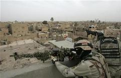 <p>Iraqi soldiers aim their weapons from a top of a building during a military operation in Baghdad's al-Fadhil district March 30, 2009. REUTERS/Saad Shalash</p>