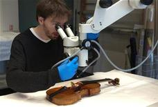 <p>Jean-Philippe Echard, Music museum research engineer, works on a 1708 Stradivarius violin at his laboratory at the Cite de la Musique in Paris, December 4, 2009. Echard and a team of scientists from various French and German institutions shine a light on the mystery of Stradivarius violin's legendary varnish : Antonio Stradivari used completely common and easily obtained materials that were broadly used in 18th century decorative arts and paintings. REUTERS/Philippe Wojazer</p>