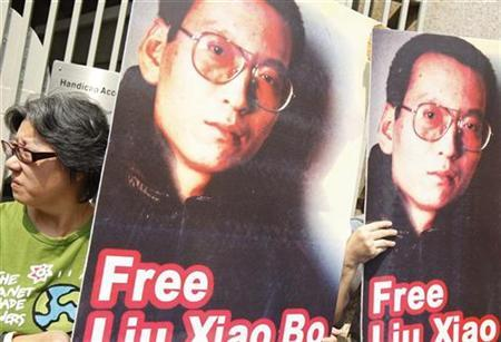 Demonstrators hold pictures of Chinese dissident Liu Xiaobo during a protest, urging Nobel peace prize recipient U.S. President Barack Obama to demand the Chinese government to release all dissidents, outside the U.S. Consulate General in Hong Kong October 23, 2009. REUTERS/Tyrone Siu