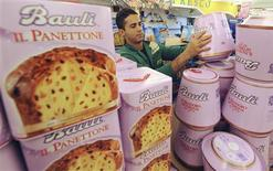 <p>A worker arranges a display of Panettone cakes at a supermarket in Rome December 18, 2009. REUTERS/Alessandro Bianchi</p>