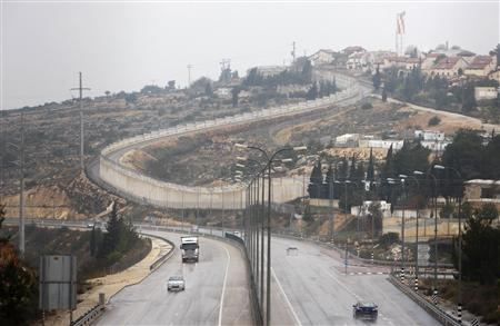 Vehicles drive on Highway 443 past the West Bank Jewish settlement of Beit Horon (R) December 30, 2009. REUTERS/Ammar Awad