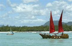 <p>A Mauritian fishing boat sails past the 'Flor de la Mar', a small replica of a pirate galleon, taking tourists along the East coast of Mauritius towards Ile aux Cerfs which has one of the most picturesque and spectacular beaches on the Indian Ocean island, November 13, 2003. REUTERS/Darrin Zammit Lupi</p>