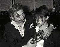 """<p>Foto de archivo del cantante francés Serge Gainsbourg y su hija Charlotte tras la entrega de los premios César en París, Feb 23 1986. Serge Gainsbourg, fumador empedernido y autor del clásico """"Je t'aime moi non plus"""" y de una versión reggae de """"La Marseillaise"""", se sumará la próxima semana a Edith Piaf y Coco Chanel como una de las figuras francesas cuya vida será llevada a la pantalla. REUTERS/Frederic de la Mure</p>"""