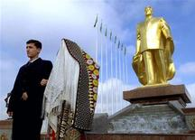 <p>Молодожены позируют у золотой статуи экс-президента Туркмении Сапармурата Ниязова в Ашхабаде 28 декабря 2002 года. Президент Туркмении Курбанкули Бердымухамедов распорядился убрать золотую статую своего предшественника Сапармурата Ниязова из столицы страны Ашхабада. REUTERS/Shamil Zhumatov</p>