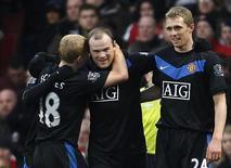 <p>Wayne Rooney do Manchester United (centro) comemora gol com colegas em jogo da Copa da Liga Inglesa contra o Arsenal no estádio Emirates em Londres. O Manchester United demonstrou com ênfase arrasadora suas intenções no campeonato inglês ao derrotar o rival Arsenal por 3 x 1 neste domingo. REUTERS/Eddie Keogh 31/01/2010</p>
