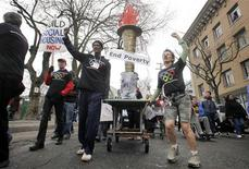<p>Anti-poverty protestors march their version of the Olympic Torch through the streets of Vancouver, British Columbia February 7, 2010. REUTERS/Andy Clark</p>