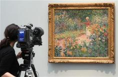 <p>A TV camera woman takes pictures of the painting 'Monet's garden at Giverny' from 1895 by late French artist Claude Monet (1840-1926) during a media preview at the Kunsthaus Zurich in Zurich, February 9, 2010. REUTERS/Arnd Wiegmann</p>