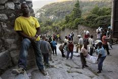 <p>Earthquake survivors carry sacks of rice during food distribution in Port-au-Prince February 10, 2010. REUTERS/Ivan Alvarado</p>