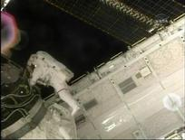 <p>L'astronauta Robert Benhken lavora sullo shuttle Endeavour. REUTERS/NASA TV</p>