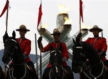 <p>Members of the Royal Canadian Mounted Police (RCMP) Musical Ride stand in front of the Olympic cauldron at the Vancouver 2010 Winter Olympics, February 23, 2010. REUTERS/Lyle Stafford</p>