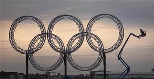 <p>Рабочие меняют лампочки в олимпийских кольцах в Ванкувере 28 января 2010 года. Россия занимает пятое место в общем медальном зачете. REUTERS/Andy Clark</p>