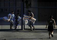 <p>Мародеры с добычей в Сантьяго 28 февраля 2010 года. Из-за участившихся случаев мародерства чилийские власти продлили комендантский час в Консепсьоне, который пострадал в минувшую субботу от мощнейшего землетрясения. REUTERS/Marco Fredes</p>
