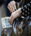 <p>Женщина кладет деньги в сумку в Токио 16 октября 2008 года. В Тульской области грабитель, уходя от преследования, оказал яростное сопротивление и укусил заместителя прокурора города Щекино, сообщает сайт местной прокуратуры www.prokuror-tula.ru. REUTERS/Kim Kyung-Hoon/Files</p>