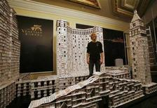<p>Bryan Berg of the U.S. poses with a replica of the Venetian Macao (C) and adjacent constructions built from freestanding playing cards at the Venetian Macao resort hotel in Macau March 10, 2010. Berg broke his own Guinness World of Records for the largest house of freestanding playing cards on Wednesday after a 44-day attempt by using 218,792 cards to build the project, which measures 10.5 meters (34 feet) long, three meters (10 feet) tall and weighs more than 272 kilograms (600 pounds). Picture taken through glass window. REUTERS/Bobby Yip</p>