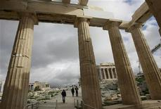 <p>Visitors walk behind Propylaia, the ancient Acropolis gateway, as the Parthenon temple (R) is seen in the background in Athens, January 5, 2010 file photo. REUTERS/John Kolesidis</p>
