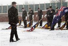 <p>Standard bearers wait under falling snow during the service for the re-burial of soldiers killed in the battle of Fromelles at Pheasant Wood military cemetery in Fromelles, northern France January 30, 2010. The battle of Fromelles took place on July 19, 1916. REUTERS/Pascal Rossignol</p>