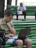 <p>Uomo legge il giornale mentre un secondo lavora al computer, foto d'archivio. REUTERS/Gleb Garanich</p>