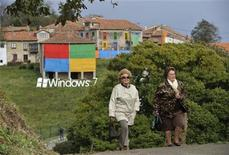 <p>Two women walk in front of the decorated village of Sietes during the presentation of Windows 7, in the northern Spanish region of Asturias, October 22, 2009. REUTERS/Eloy Alonso</p>