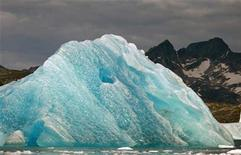 <p>A deep blue iceberg floats in a fjord south of Tasiilaq in eastern Greenland August 2, 2009. The blue color is a result of compression and repeated thawing and refreezing. REUTERS/Bob Strong</p>