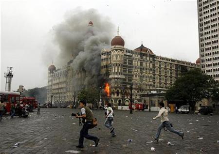 Photographers run past burning Taj Mahal Hotel during a gun battle in Mumbai November 29, 2008. REUTERS/Arko Datta