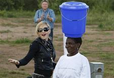 <p>Pop star Madonna brinca ao observar uma mulher carregar um balde com água na cabeça durante sua visita ao Malauí. 05/04/2010 REUTERS/Mike Hutchings</p>
