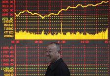 <p>Un investitore sorride di fronte ad uno schermo elettronico con le informazioni azionarie, REUTERS/Stringer</p>