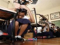 <p>Ученики одной из начальных школ Филиппин сидят под партами во время землетрясения, 17 февраля 2010 года. Землетрясение силой 6,9 балла по шкале Рихтера произошло в океане в 300 километрах к северу от Филиппинских островов в понедельник и ощущалось на Тайване, однако сведений о разрушениях пока нет, сообщили власти. REUTERS/Erik de Castro</p>