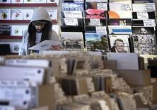 <p>Un uomo guarda un disco in un negozio a Londra REUTERS/Luke MacGregor</p>