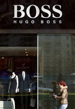 A shopper walks past a Hugo Boss store in central Beijing March 17, 2010. REUTERS/David Gray