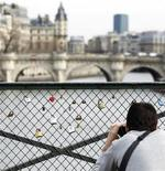 <p>A tourist takes a picture of padlocks, placed there by lovers, on the Pont des Arts' bridge on the Seine river in Paris, March 17, 2010. REUTERS/Charles Platiau</p>