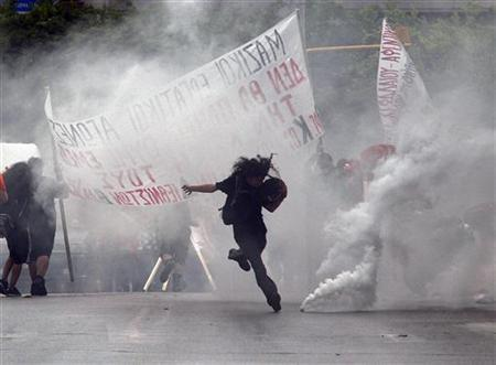 A protestor kicks a teargas canister during violent demonstrations over austerity measures in Thessaloniki, May 5, 2010. REUTERS/Grigoris Siamidis