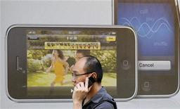 <p>Un utente asiatico con telefonino davanti ad una pubblicità dell'iPhone. REUTERS/Toby Melville</p>