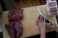 <p>Macellaio mentre taglia la carne, foto d'archivio. REUTERS/Carlos Garcia Rawlins</p>