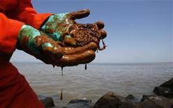 <p>Petróleo cae de los guantes de goma de un biólogo marino de Greenpeace, mientras muestra la contaminación en la desembocadura del río Misisipi, donde se junta con el Golfo de México, en Lusiana. Mayo 17 2010. El descubrimiento de bolas de alquiltrán en Key West, en Florida, alimentó el temor en Estados Unidos de que el enorme derrame de crudo del Golfo de México se esté extendiendo por las corrientes oceánicas, mientras el gigante de energía BP trabaja para reducir la fuga de su pozo submarino. REUTERS/Hans Deryk</p>