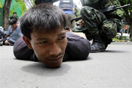 A detainee lies on the ground during an operation to evict anti-government ''red shirt'' protesters from their encampment in Bangkok May 19, 2010. REUTERS/Sukree Sukplang