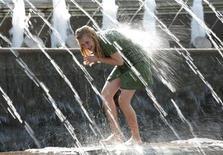 <p>Девушка купается в фонтане в Александровском саду в Москве 14 июня 2006 года. Грядущие выходные в Москве будут теплыми, горожане увидят и солнце, и тучи. REUTERS/Eduard Korniyenko</p>