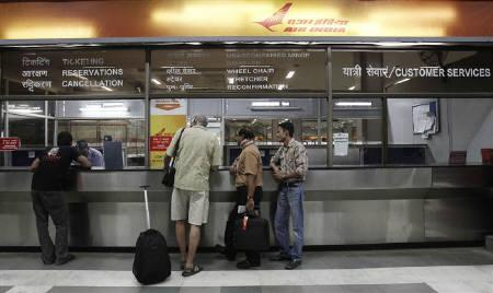 Stranded passengers stand outside the Air India counter at the domestic airport in New Delhi May 25, 2010.REUTERS/Adnan Abidi