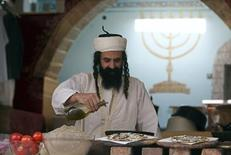 <p>An ultra-Orthodox Jew adds olive oil to pizza before serving it to customers in his restaurant in the northern town of Safed May 26, 2010. REUTERS/Nir Elias</p>